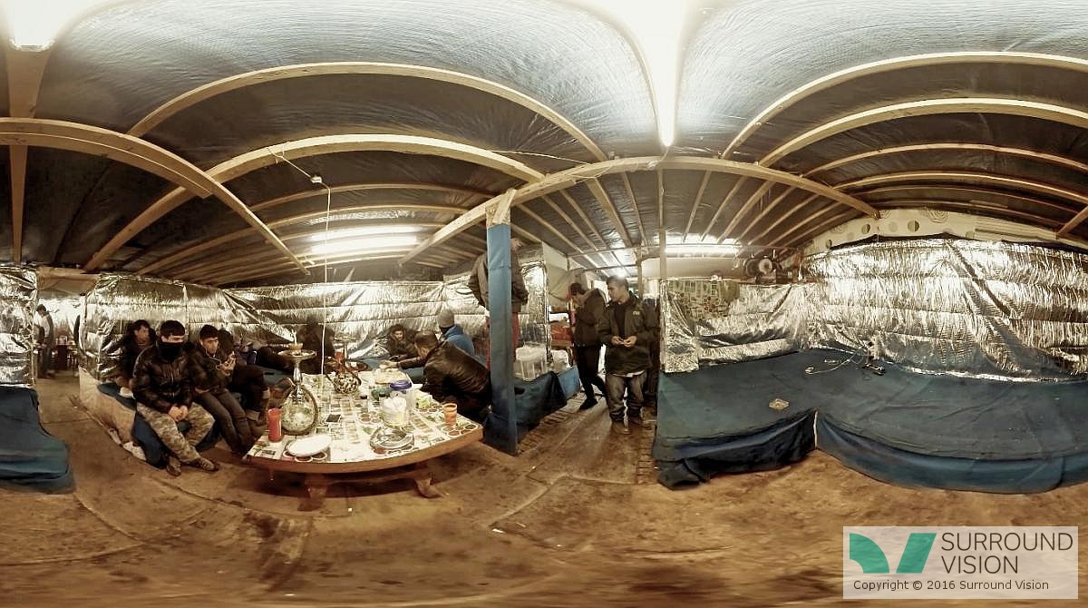 """Men are sitting in the cold inside a makeshift house in """"The Jungle"""" in Calais France, from the Surround Vision VR 360 degree production with SKY of """"Home: Aamir"""""""