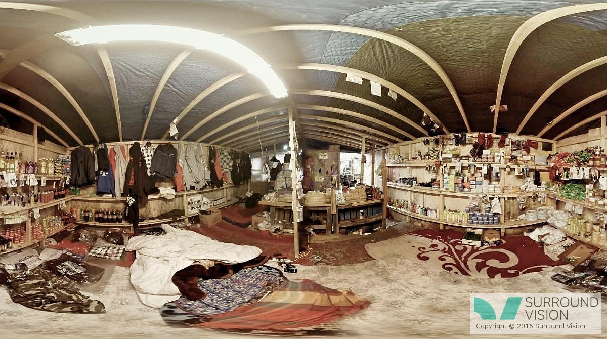 """Inside a house constructed in """"The Jungle"""" in Calais France, walls are packed with clothes and shelves of food"""