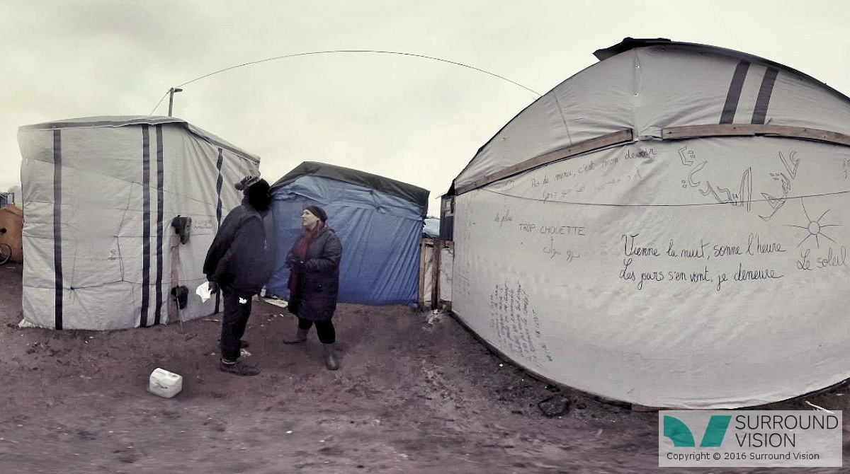 """Surround Vision staff memebr talks to an inhabitants of """"The Jungle"""" in Calais France, from the Surround Vision VR 360 degree production """"Home: Aamir"""""""