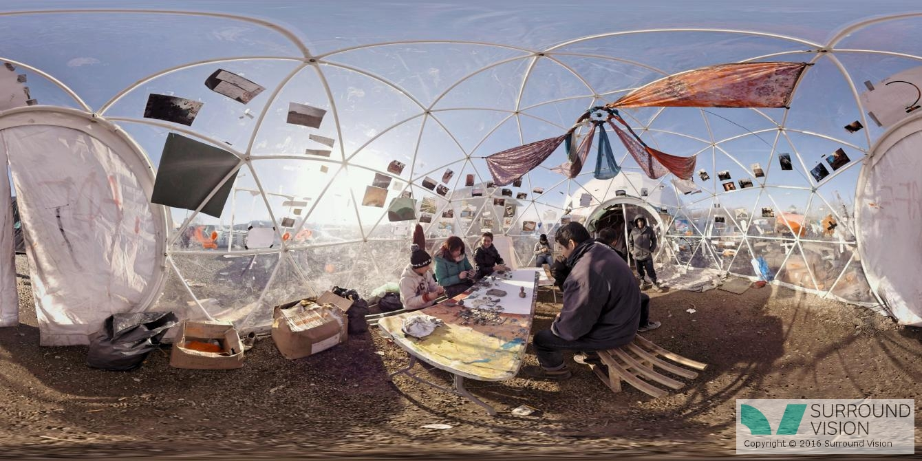 """People sit inside a poytube construction of a geodesic dome at """"The Jungle"""" in Calais France, from the Surround Vison VR production of """"Home: Aamir"""""""